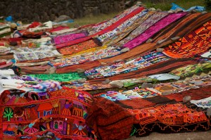 Peru_-_Cusco_Sacred_Valley_&_Incan_Ruins_039_-_textile_handcrafts_for_sale_at_Tambomachay_(7092596219), McKay Savage, CC BY 2.0. Wikim. Comm.